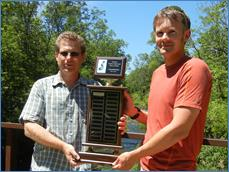 SEWISC Board President Brian Russart presents Shawn Graff OWLT Executive Director with the Annual Pull-A-Thon Traveling Trophy